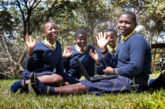 Feature Image shows Kuwala Campus Girls waving with new donated laptops