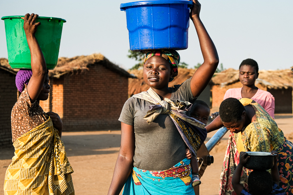 Image of village life. Girl carrying water from the village