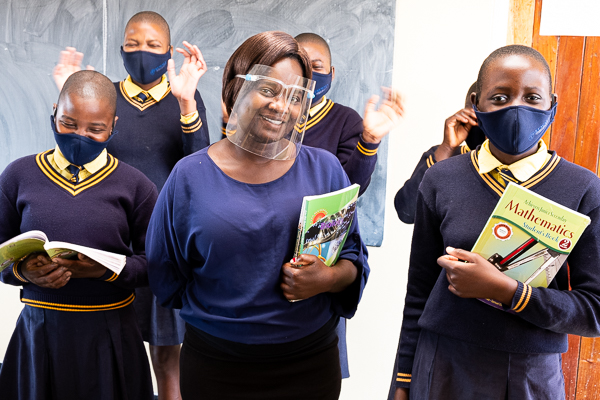 Image of Kuwala teacher surrounded by students wearing masks and PPE