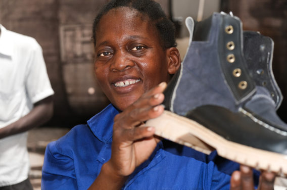 Image of Trogon Boot Factory employee showing off a boot made in Malawi, Africa