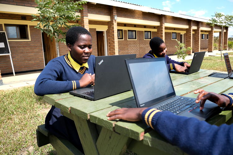 Image of Kuwala students outside with their newly donated laptops from Canada.