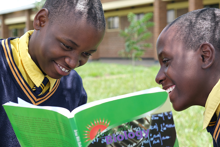 Image of two Kuwala students looking into a Buology workbook.