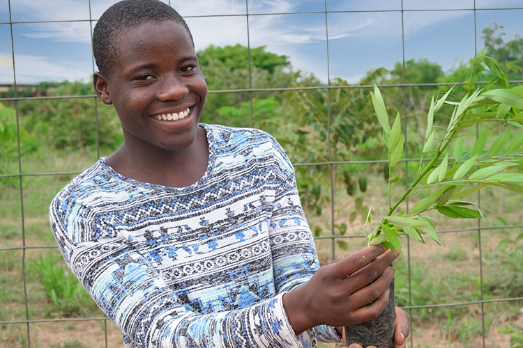 Image of Kuwala student smiling as she is holding a tree she is about to plant.