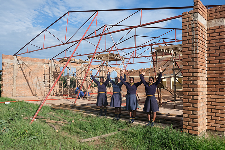 Image of raising the rafters in the Kuwala campus dining hall with girls underneath rafters.