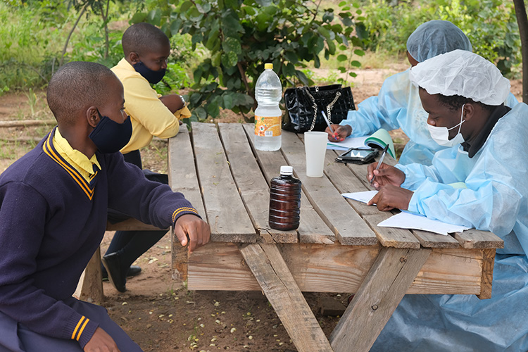 Image of Malawian Health Care team checking students for Covid19