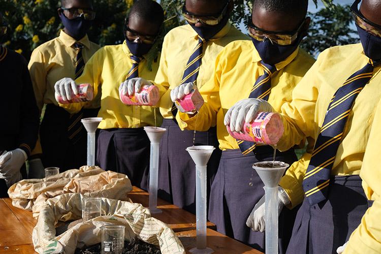 Image of Kuwala students testing soil outside using new lab equipment.