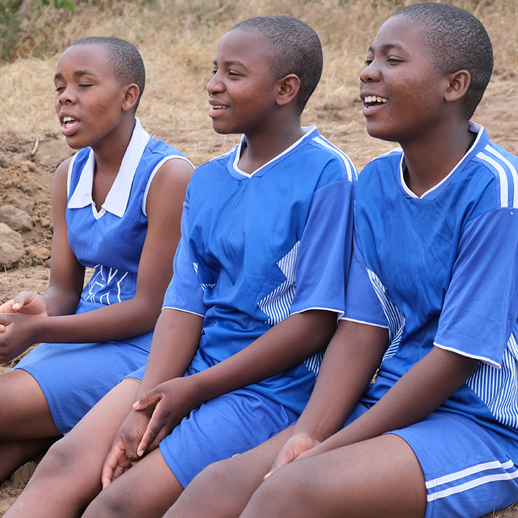 Image of Kuwala girls on the side line watching the soccer game unfold.