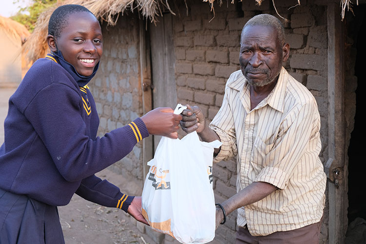 Kuwala student with elder Jonas handing over a care package as part of the village outreach program.