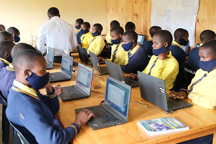 Kuwala students studying with computers and workbooks