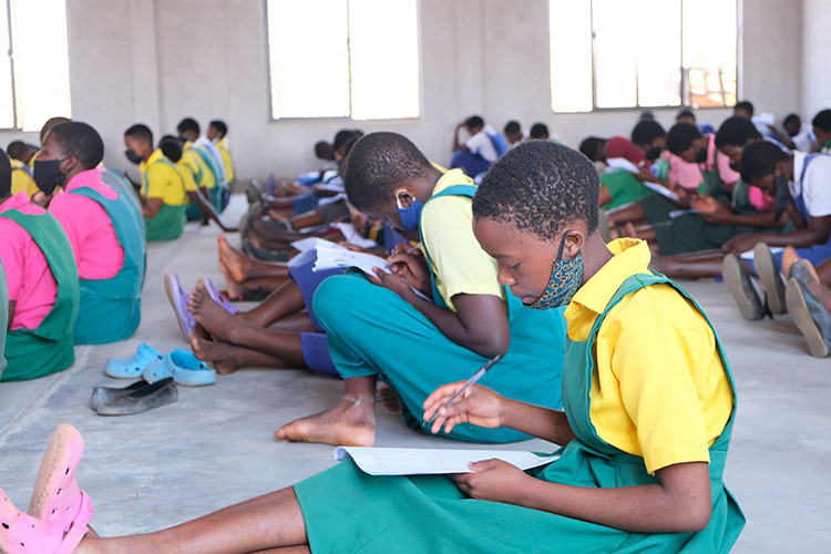 Potential Kuwala student candidates writing the exam on the floor of St. Peter's Assembly Hall.