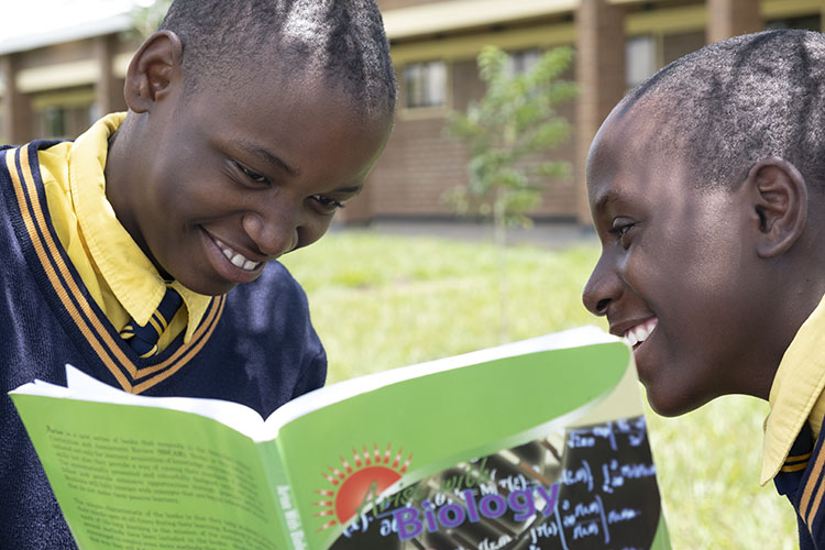 Two Kuwala students sharing a text book with smiles on the faces.